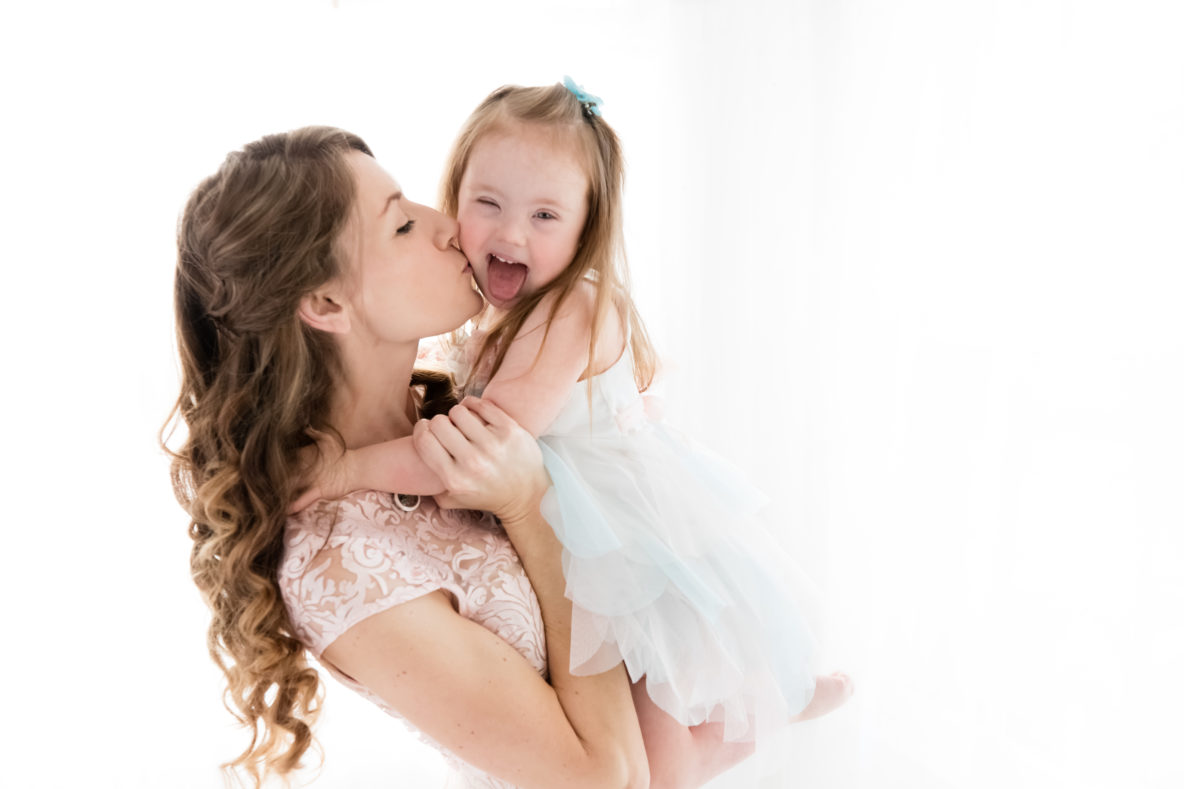 mom kissing daughter with down syndrome